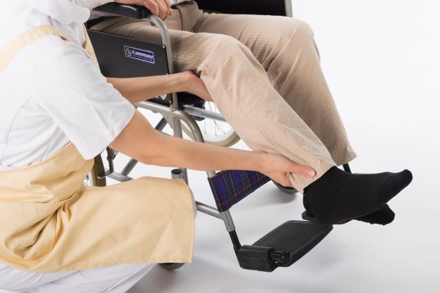 車椅子に乗せる介護士