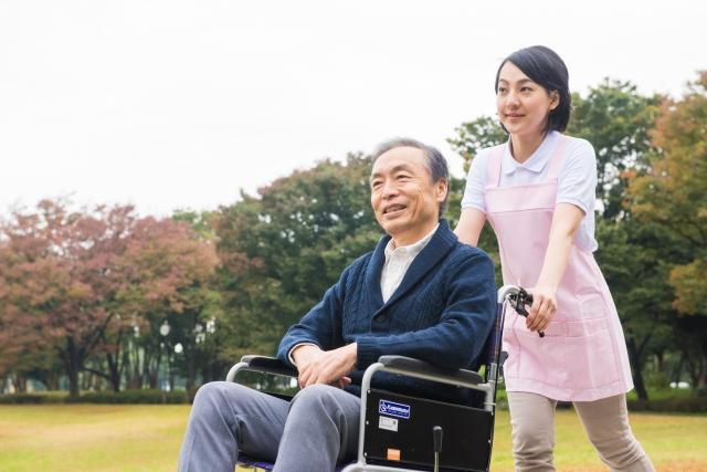 公園で車椅子を押す介護士