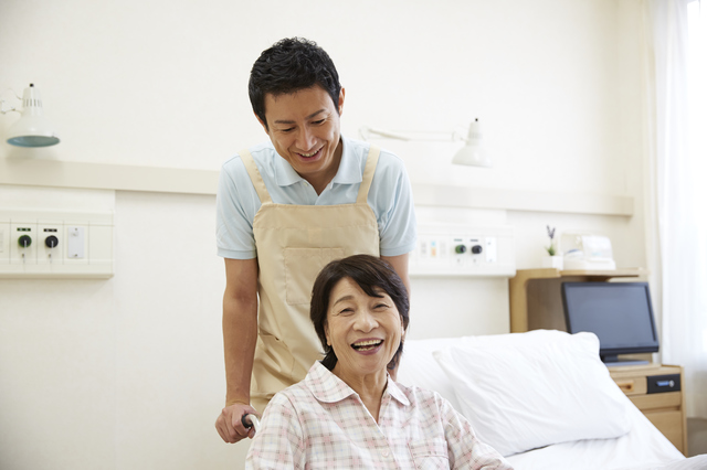 車椅子を押す介護職職員
